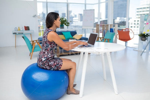 Vrouwelijke uitvoerende met behulp van laptop vergadering oefening bal Stockfoto © wavebreak_media