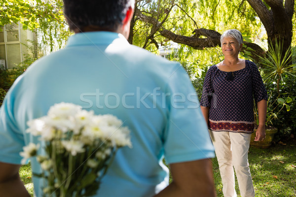 Mid-section of senior man hiding flowers behind back Stock photo © wavebreak_media