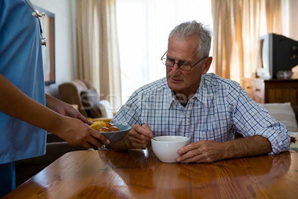 Stock photo: Female doctor serving food to senior man in nursing home