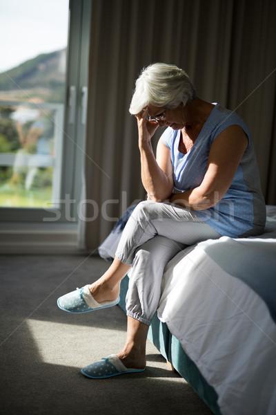 Tenso senior mulher sessão cama quarto Foto stock © wavebreak_media