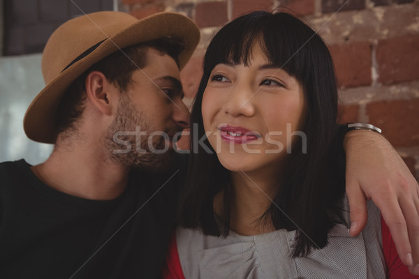 Young man whispering in woman ear at cafe Stock photo © wavebreak_media