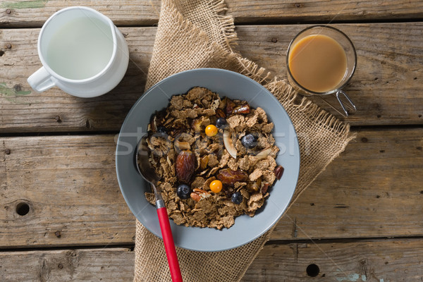 Bowl of wheat flakes, blueberry and golden berry with milk jug Stock photo © wavebreak_media