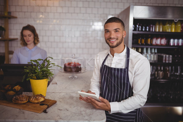 Portrait of smiling young waiter using digital tablet while standing by counter Stock photo © wavebreak_media