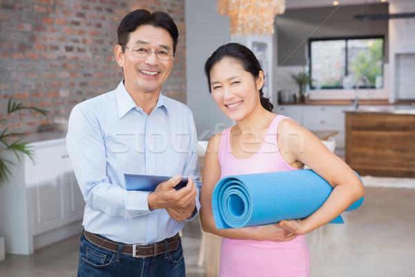 Happy couple using tablet and holding mat Stock photo © wavebreak_media