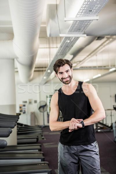 Smiling man on treadmill looking at smartwatch Stock photo © wavebreak_media