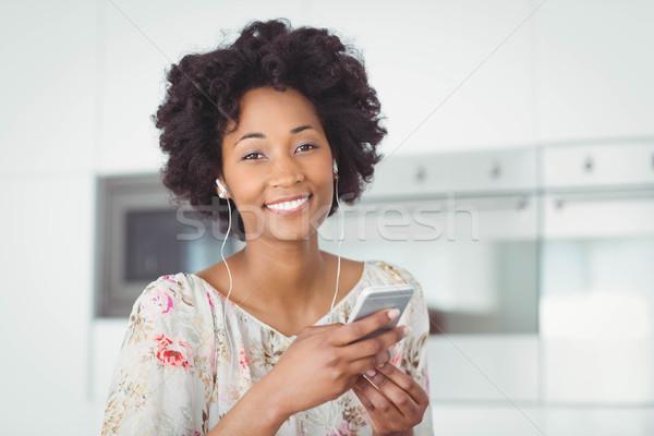 Mosolygó nő fülhallgató okostelefon konyha nő zene Stock fotó © wavebreak_media