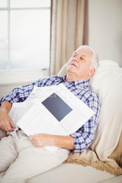 Altos hombre relajante sofá periódico salón Foto stock © wavebreak_media