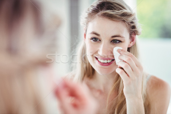 Happy young woman applying blush Stock photo © wavebreak_media