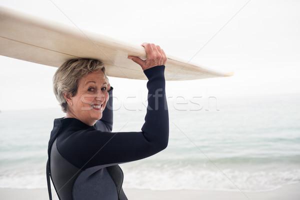 Senior woman in wetsuit carrying surfboard over head Stock photo © wavebreak_media