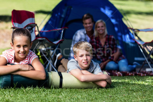 Siblings lying on grass outside the tent Stock photo © wavebreak_media