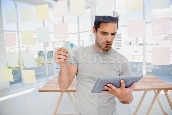Hombre mirando digital tableta notas adhesivas oficina Foto stock © wavebreak_media