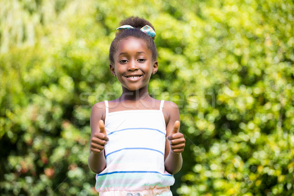 Mixed-race girl smiling and throwing up thumbs Stock photo © wavebreak_media