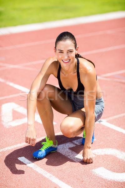 Portrait of female athlete kneeling on running track Stock photo © wavebreak_media