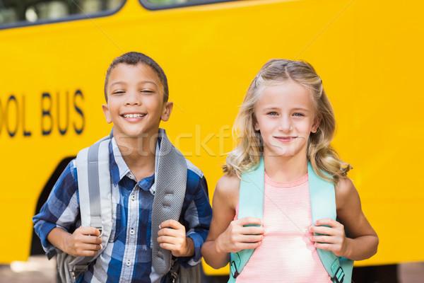 Smiling kids standing in front of school bus Stock photo © wavebreak_media