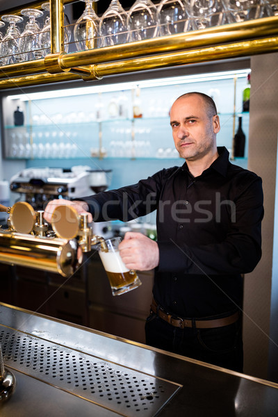 Brewer filling beer in beer glass from beer pump Stock photo © wavebreak_media