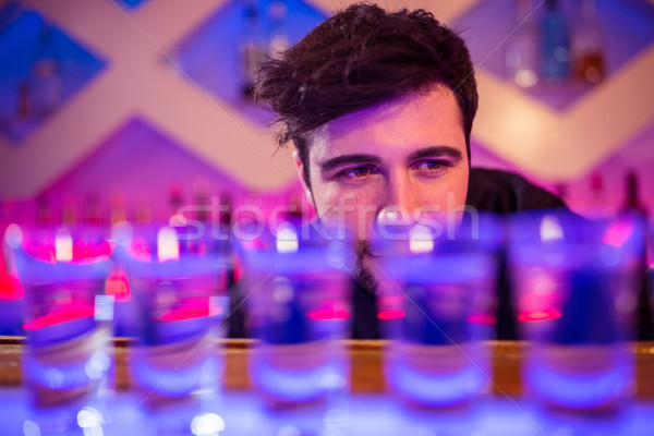 Bartender looking at shot glasses on counter Stock photo © wavebreak_media