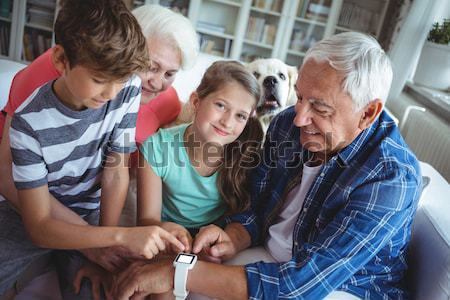 Grandparents and grandchildren looking at smartwatch in living room Stock photo © wavebreak_media