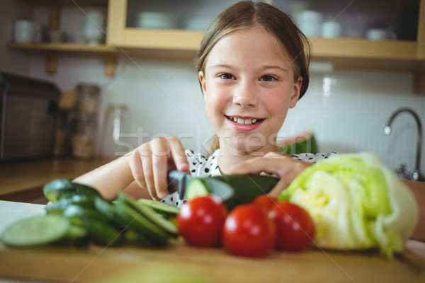 Girl cutting zucchini in kitchen at home Stock photo © wavebreak_media