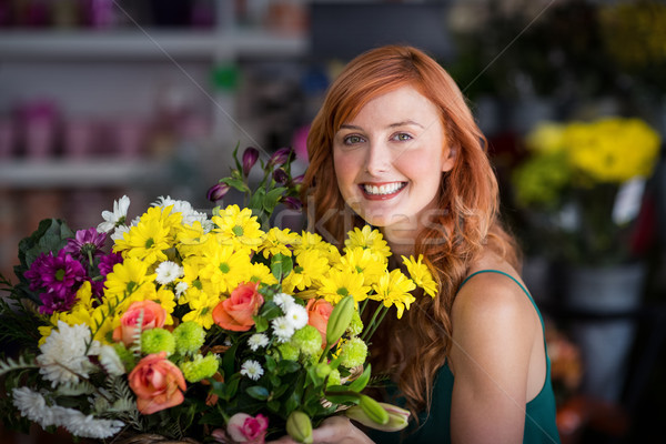 Happy female florist holding bunch of flowers Stock photo © wavebreak_media