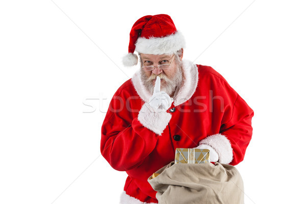 Santa claus with finger on lips and holding a gifts Stock photo © wavebreak_media