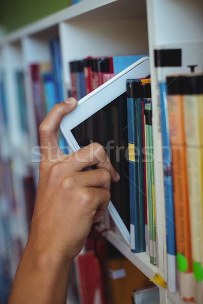 Mão estudante digital comprimido prateleira de livros biblioteca Foto stock © wavebreak_media