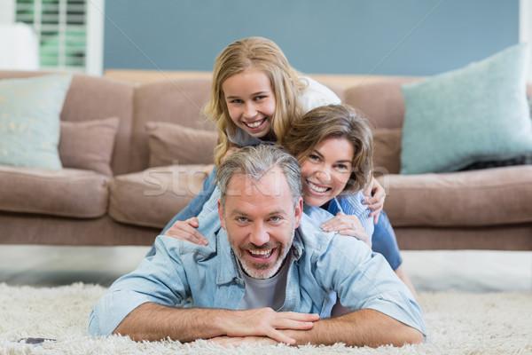 Portrait of happy family lying heaped on carpet in living room Stock photo © wavebreak_media