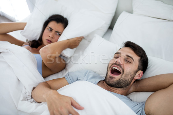 Woman getting disturbed with man snoring on bed Stock photo © wavebreak_media