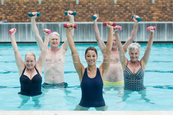 Female instructor with senior swimmers exercising in swimming pool Stock photo © wavebreak_media