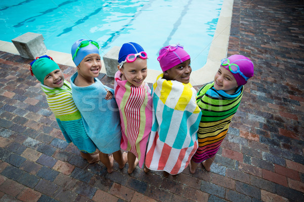 Rear view of little swimmers wrapped in towels at poolside Stock photo © wavebreak_media