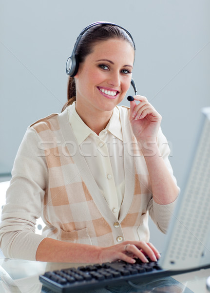 Self-assured businesswoman with headset on working at a computer Stock photo © wavebreak_media