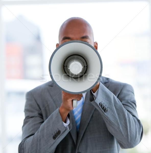 Ethnic businessman yelling through a megaphone Stock photo © wavebreak_media