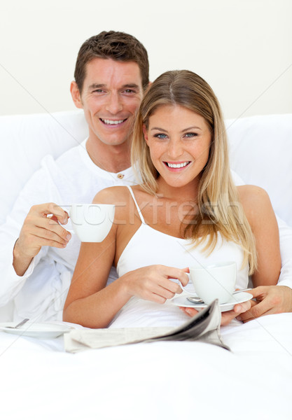 Stock photo: Happy couple drinking coffee lying on their bed