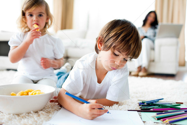 Cute little gir eating chips and her brother drawing Stock photo © wavebreak_media