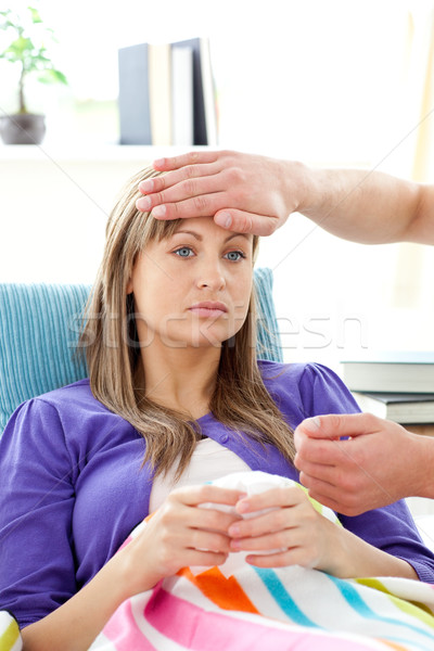 Man feel the temperature of his girlfriend lying on a sofa Stock photo © wavebreak_media