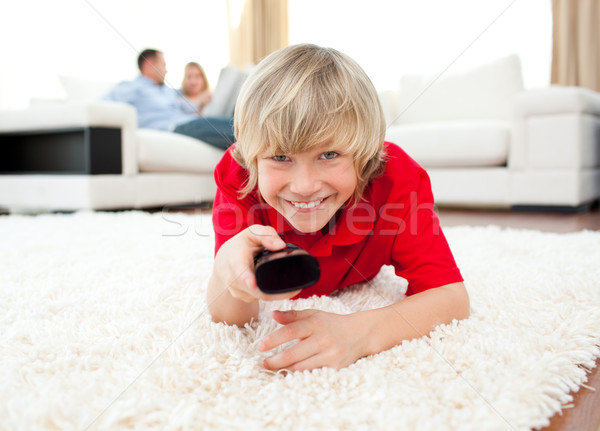 Happy boy holding a remote lying on the floor in the living-room Stock photo © wavebreak_media