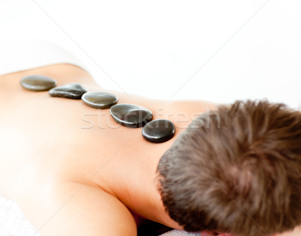 Young caucasian relaxing man with hot stone on his back in  a spa center Stock photo © wavebreak_media