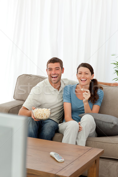 Cute couple eating pop corn while watching television on the sofa at home Stock photo © wavebreak_media