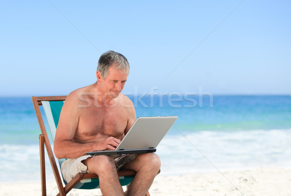 Retired man working on his laptop on the beach Stock photo © wavebreak_media