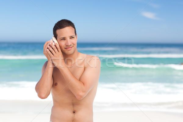 Homme écouter shell heureux mer fond Photo stock © wavebreak_media