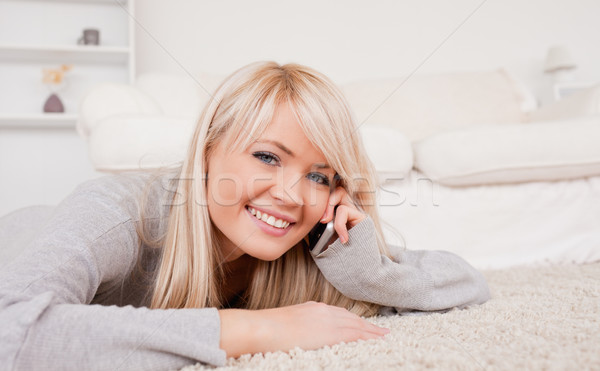 Stock photo: Attractive happy blond woman talking on cell phone lying down on a carpet in the living room