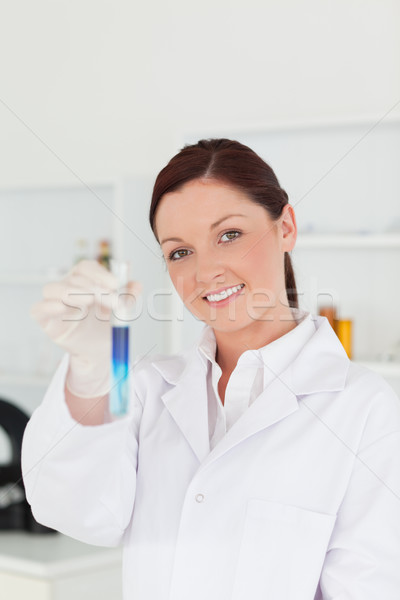 Good looking red-haired scientist looking at the camera while holding a test tube in a lab Stock photo © wavebreak_media