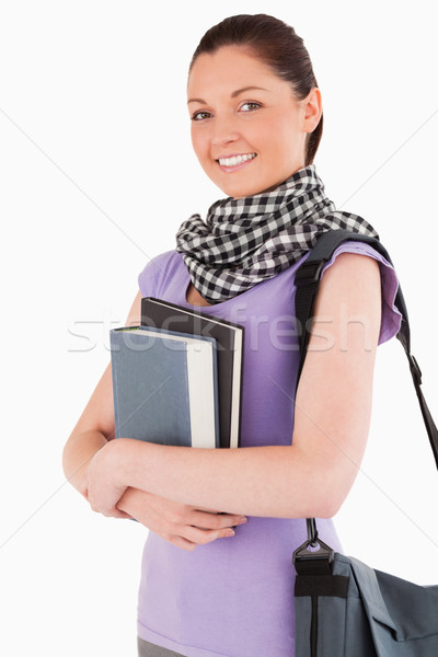 Charming student holding books and her bag while standing against a white background Stock photo © wavebreak_media