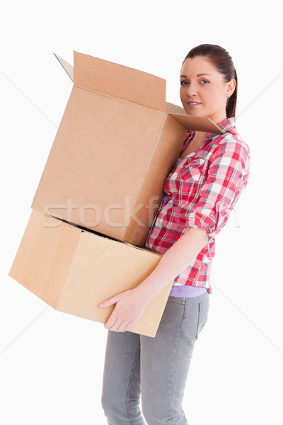 Good looking woman holding cardboard boxes while standing against a white background Stock photo © wavebreak_media