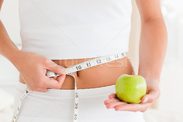 woman measuring her waist while holding an apple in bedroom Stock photo © wavebreak_media