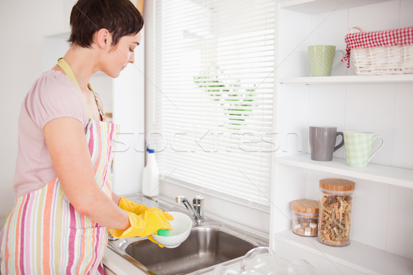 Beautiful brunette woman washing the dishes in the kitchen Stock photo © wavebreak_media