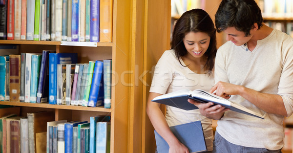 Smiling students looking at a book in a library Stock photo © wavebreak_media
