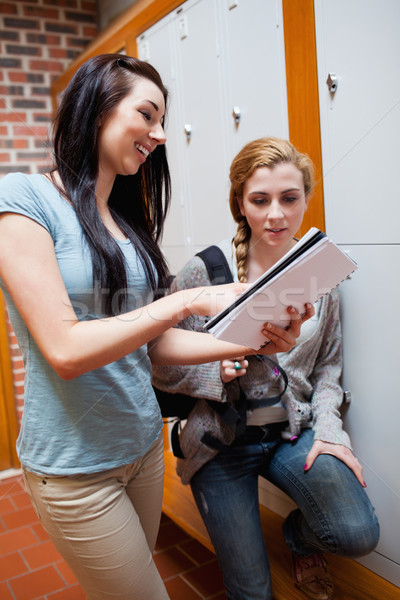 Portrait of a student showing her notes to her friend in a corridor Stock photo © wavebreak_media
