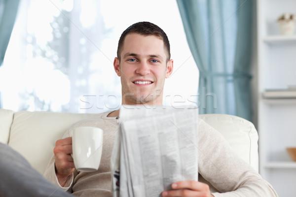 молодым человеком чай чтение Новости гостиной бумаги Сток-фото © wavebreak_media