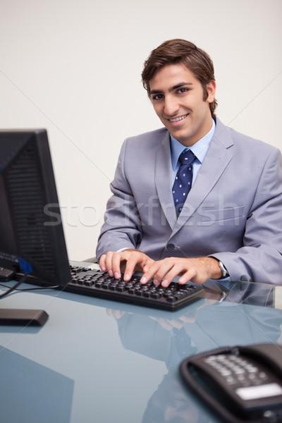 笑みを浮かべて 小さな ビジネスマン 入力 キーボード 作業 ストックフォト © wavebreak_media