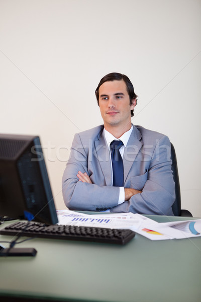Stock photo: Businessman with arms folded waiting for his computer to boot up